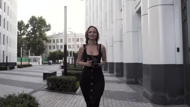 Mladá fena v dlouhých černých šatech vyfotí město a usměje se. Akce. Krásná mladá turistka chůze na pozadí budovy obchodní čtvrti s profesionální kamerou v