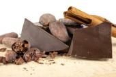 Fotografia Gustosi fagioli scuri di cacao e del cioccolato su una tavola bianca. Dolci utilizzati per preparare dolci in cucina. Priorità bassa bianca