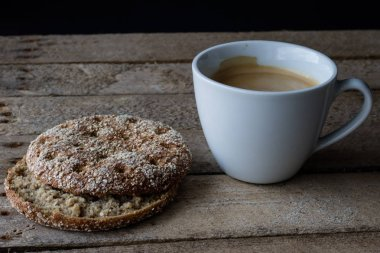 Mug with coffee and bread on a wooden table. Breakfast prepared to eat. Dark background.