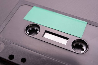 Audio cassette with space for text entry. Cassette without description. Dark background.