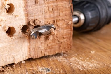 Drilling holes in raw wood. Carpentry drill in a carpentry works