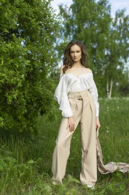 Beautiful stylish young girl wearing a trendy white shirt, beige trousers and a pareo poses outdoors against a background of green leaves. Nude makeup. Commercial and advertisement design. Copy space.