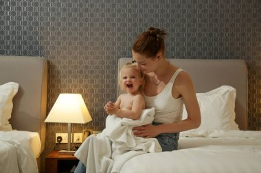 Mum and her baby girl spending time together after bathing, baby preparation for a good night's sleep.
