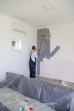 Man painting with gray paint over a white wall
