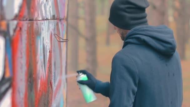 Fiatal srác rajz graffiti segítségével spray festék doboz