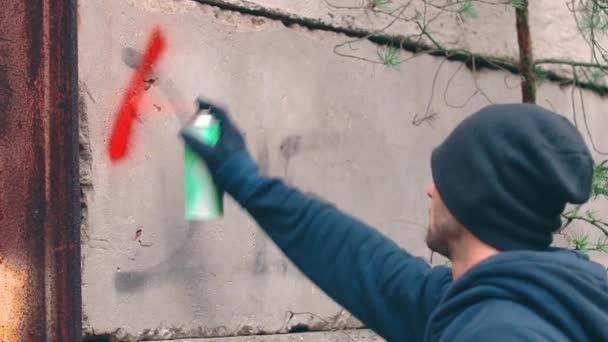 Pouliční chuligán psaní na zeď pomocí stříkací plechovky