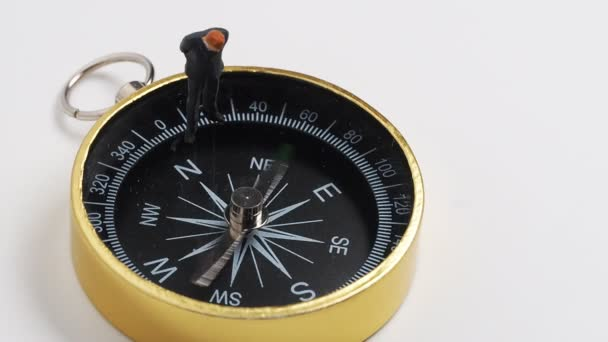 miniature figure businessman in dark blue suit standing on rotating  golden compass  for finding the way how to success of business and financial
