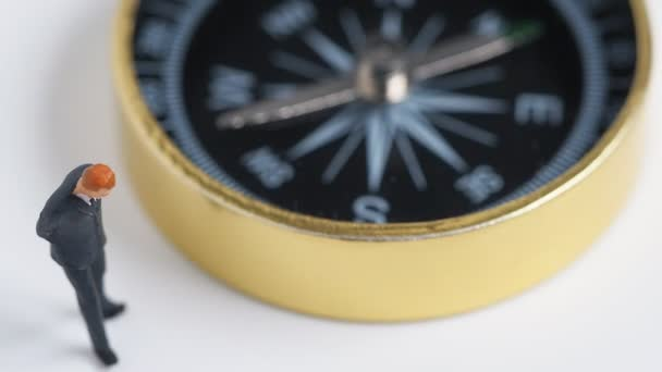 miniature figure businessman in dark blue suit standing on the side of rotating golden compass. Concept for finding the way how to success of business