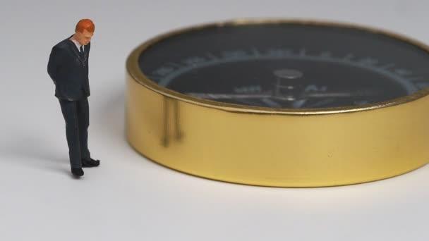 miniaturní obrázek podnikatel v tmavě modrý oblek, stojící na straně rotující Zlatý kompas. Koncept pro nalezení způsob, jak k úspěchu podnikání