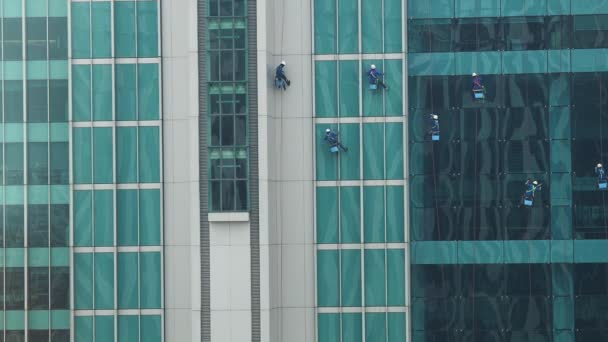 Workers hang on rope for cleaning window glass the outside of the skyscraper.