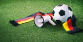 Fotografie Soccer ball with german fan scarf and megaphone on playing ground