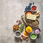 Různé barevné superpotraviny jako acai prášek, kurkuma, matcha zelený čaj, quinoa, dýňová semínka, Borůvka, sušené goji bobule, mys angreštu, kakao, semen konopí, která a další v miskách