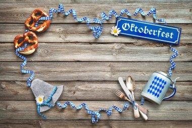 Rustic background for Oktoberfest with Bavarian white and blue streamer, pretzel, bier stein and silverware