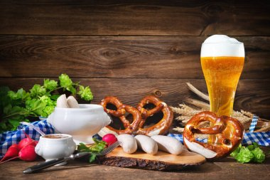 Bavarian sausages with pretzels, sweet mustard and beer on rustic wooden table. Oktoberfest menu