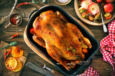 Roast Christmas duck with thyme and apples on rustic wooden table