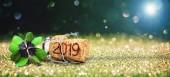 Šťastný nový rok. Blahopřání s čtyři leaf clover a šampaňského korku