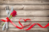 Silverware tied up with red ribbon in heart shape on wooden planks. Concept Valentines Day dinner. Restaurant party celebration