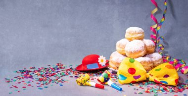 Krapfen, berliner or donuts with bow tie, party hat, streamers and confetti. Colorful carnival or birthday background