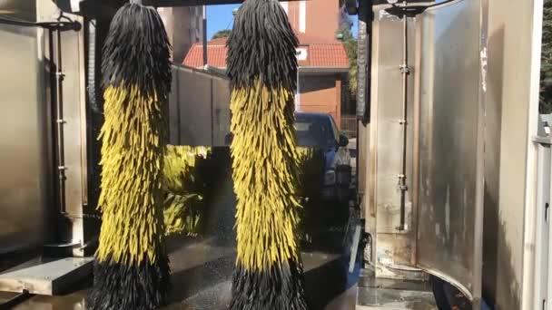 Zeitlupe des Autos, das durch Bürsten in einer Waschanlage gewaschen wird
