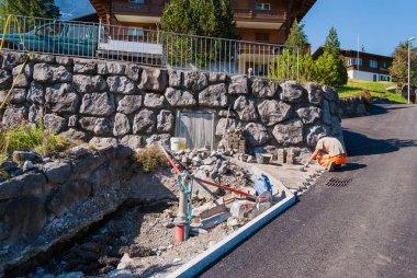 A worker lays paving slabs Grindelwald Switzerland