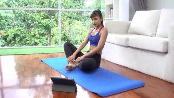 Jako asijské dívka s jóga cvičení sám v obývacím pokoji v jejím domě 4k
