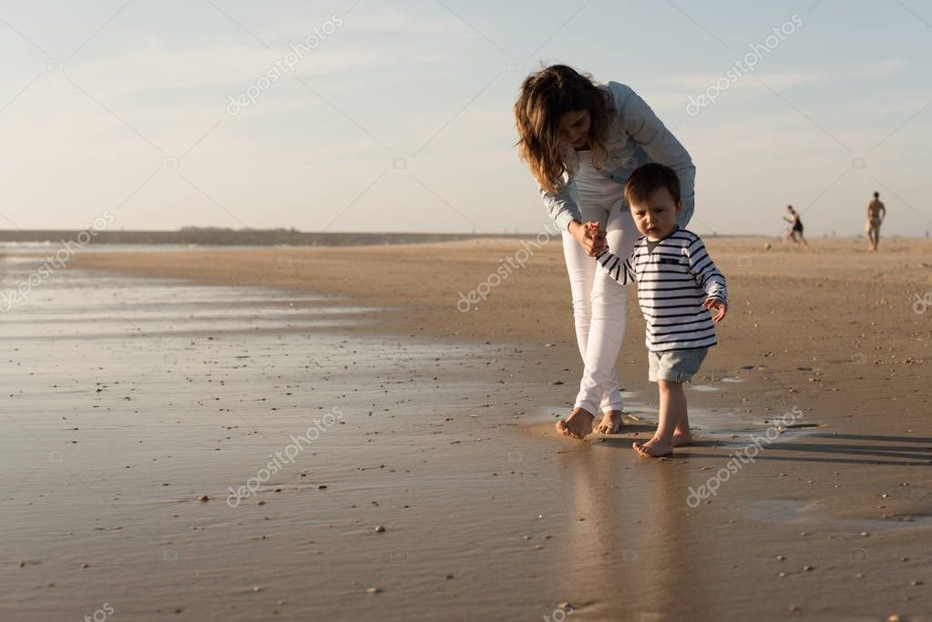 Young mother exploring the beach with toddler