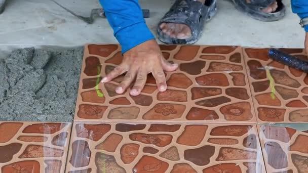 Technici si na podlaze položili dlaždice s cementem.