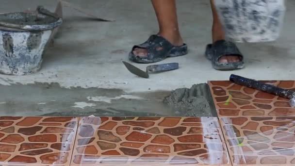 Technicians are laying tiles on the floor with cement.
