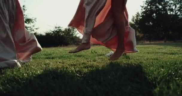 Amazing girls dancing on circle on grass , and dressed in long pink dress