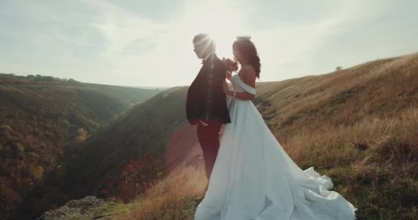 In the peak of mountain with amazing sunset bride holds her groom. 4k
