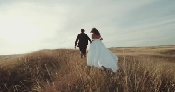 Running through the landscape beautiful groom and bride.4k