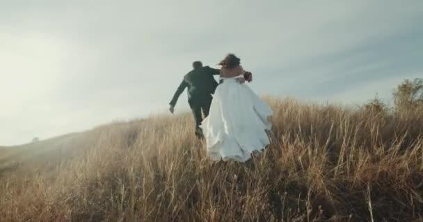 Nevěsta a ženich běží na vrcholu hory. 4k