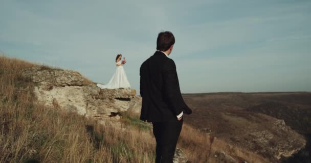 Bride and groom in the middle of mountain looking to each other.