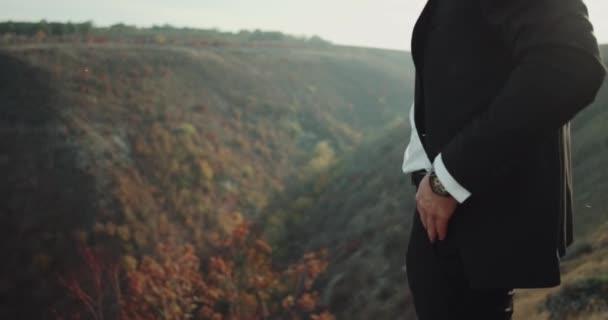 Closeup groom arrange his suit in the top of landscape .