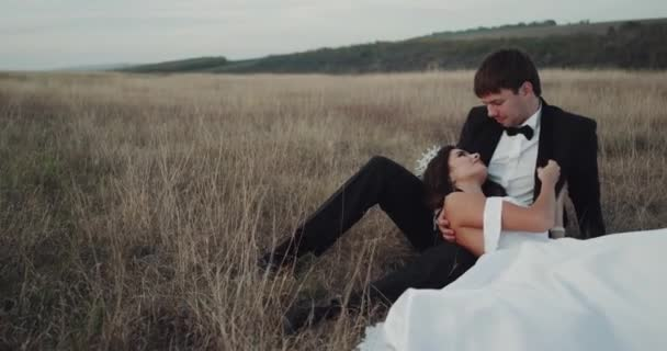 Amazing bride and groom in the middle of landscape laying down bride touching romantic his face