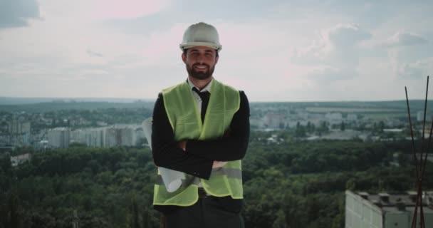 Architekt nebo Tvůrce postavit na vrcholu stavby s bezpečnostní přilbou se usmívá na kameru