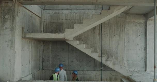 Tým inženýrů a architektů zvedněte schodech staveniště, nošení ochranné přilby