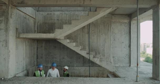Dvě odborné inženýry a stavbyvedoucí zvedněte schodech staveniště