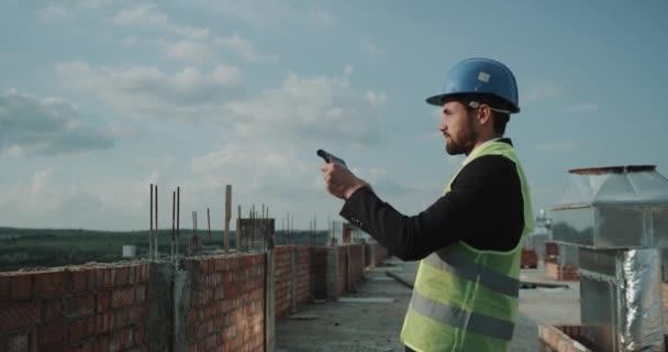 Architekt v tabletu k analýze plánu budovy na střeše budovy.