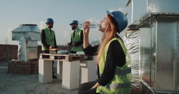 S úsměvem mladá žena na staveništi, pitnou vodu, nosit ochrannou přilbu a reflexní vesta, stavitelé pozadí pracovní