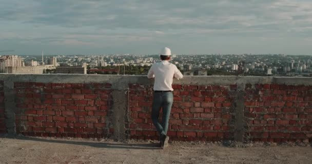 Amazing city view from rooftop building , a man with a safety helmet standup and watching around.