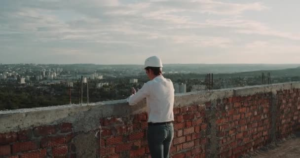 A man on construction site looking at amazing city view from rooftop.