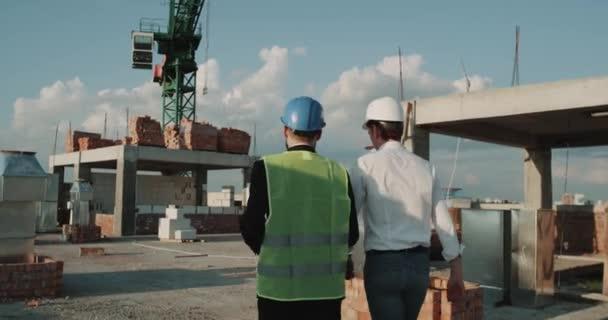 Dva mladí inženýři chůze přes staveniště, pozadí velký jeřáb, že ochranný oděv. Red epic