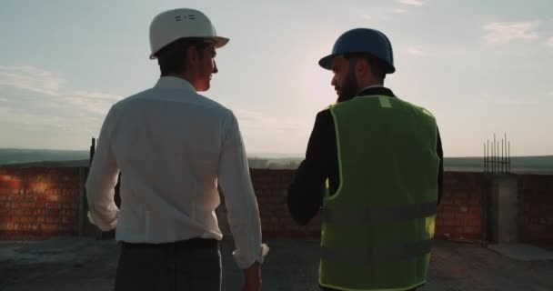 Two partners make a great deal at construction site on rooftop of building with amazing sunset