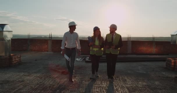 Three workers from construction site walking on rooftop of a new apartments have discussion , amazing sunset on background. Slow motions. 4k