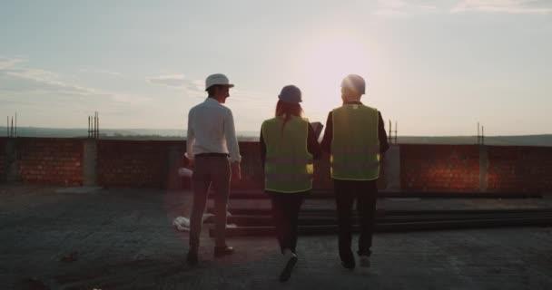 Staveniště na vrcholu budovy s úžasný západ slunce tři inženýři chodit. Pomalu Morions. 4k