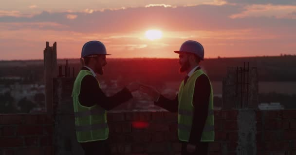 Two businessman have a great time together at construction site on rooftop playin with hands smiling , amazing sky view 4k