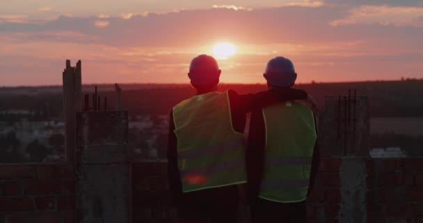 Construction site two partners looking at amazing city view and sunset , and holding like friends each other