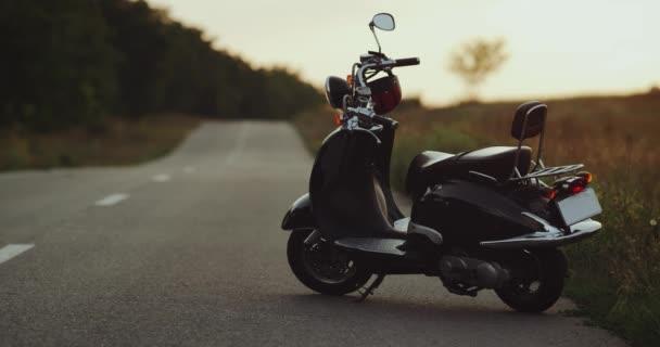 Motorka stojí na silnici s výhledem na pěkný západ slunce