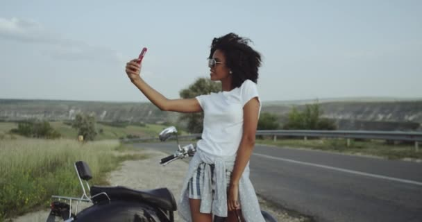 African girl with curly Afro hair takes selfies in the beautiful nature, loving that vibe